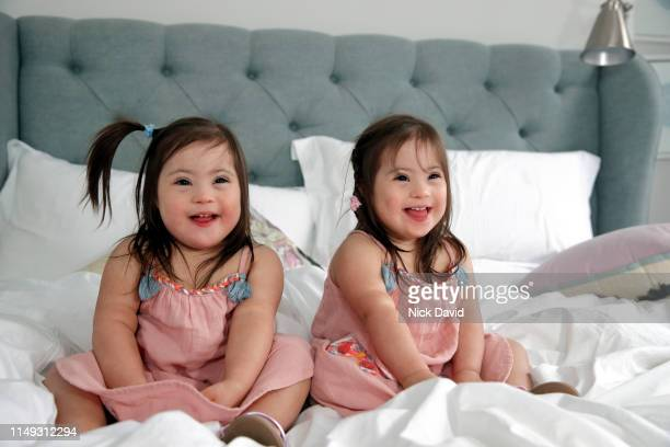 Smiling identical twin girls sitting together on bed