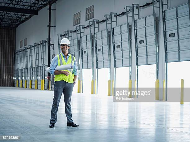 Smiling Indian architect holding blueprint near open loading dock doors