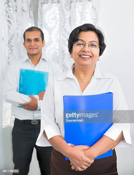 Smiling Indian Businesspeople holding office Files