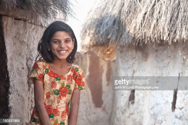Sonriente niña India está cerca de su cabaña de paja,