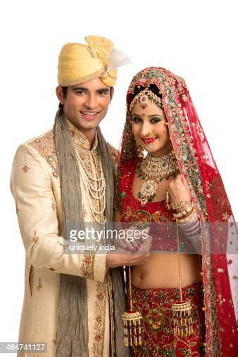 Smiling Indian Newlywed Couple In Traditional Wedding Dress Stock Photo