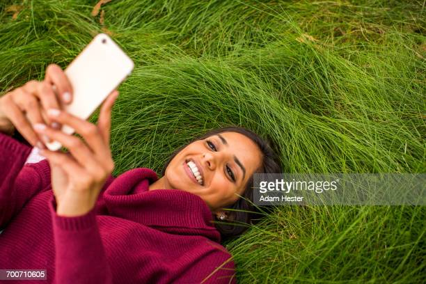 Smiling Indian woman laying in grass texting on cell phone