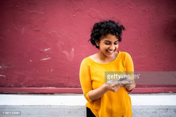 smiling indian woman using mobile phone - indian ethnicity stock pictures, royalty-free photos & images