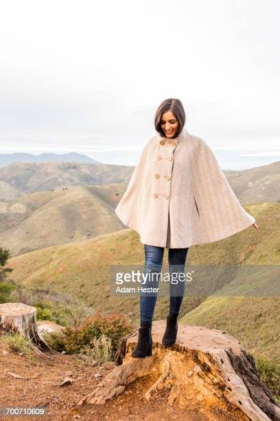 smiling indian woman wearing poncho standing on tree stump - poncho stock pictures, royalty-free photos & images