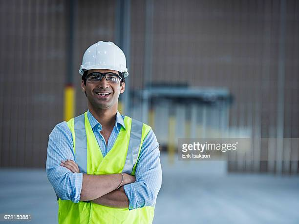 Smiling Indian worker in empty warehouse
