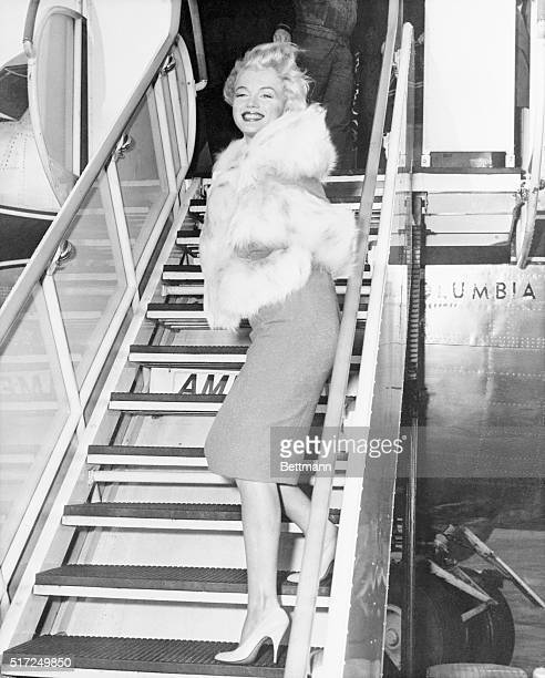 Smiling into the teeth of somewhat robust winds at New York's Idlewild airport November 2 actress Marilyn Monroe and playwrighthusband Arthur Miller...