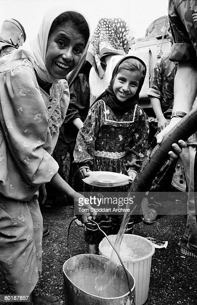 Smiling Iraqi women collect drinking water distributed by British troops in Basra, days after the city was captured during the American-led invasion...