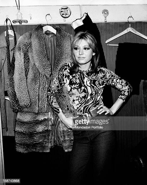 Smiling Italian singer and actress Alida Chelli born Alida Rustichelli poses in a dressing room her hands on her hips behind her on a coatstand are...
