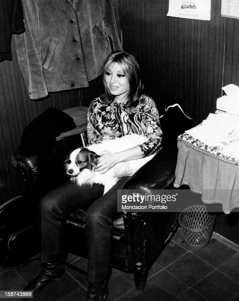 Smiling Italian singer and actress Alida Chelli born Alida Rustichelli sits in an armchair and holds a little dog in her arms Turin 1968