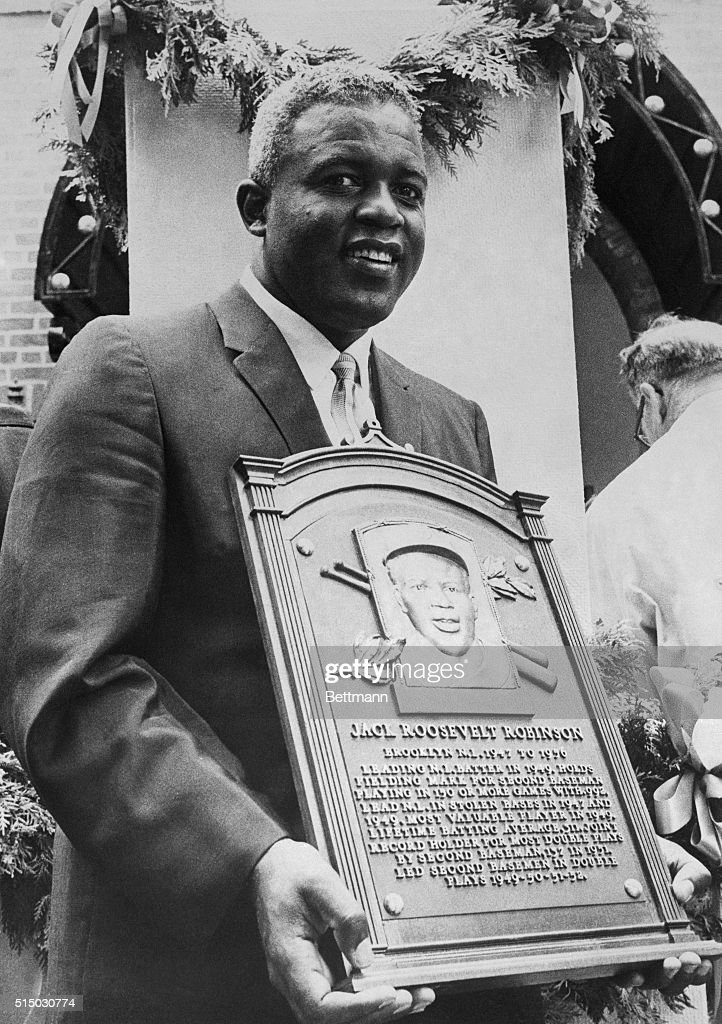 Smiling Jackie Robinson, who broke baseball's color line in 1947, holds a plaque after he was inducted into baseball's Hall of Fame here 7/23.