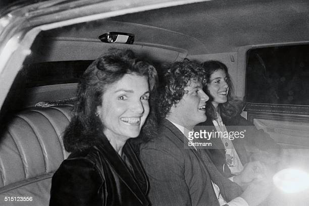 A smiling Jacqueline Kennedy Onassis sits in limousine with her two children John Jr and Caroline after attending the dedication reception at the...