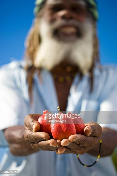 Smiling Jamaican man with Ackee fruit