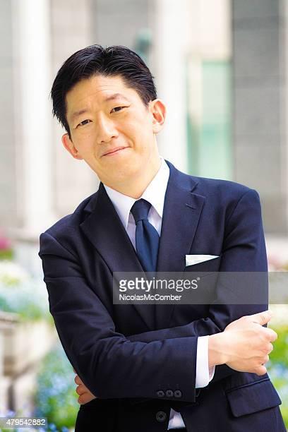 笑顔の日本の実業家の肖像画屋外腕を組む