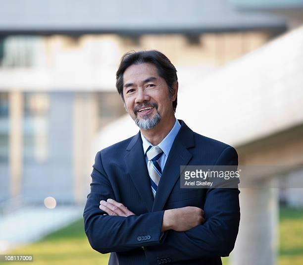 笑顔日本のビジネスマンが腕を組む