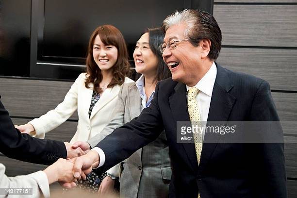 Smiling Japanese businessmen and businesswomen shaking hands.