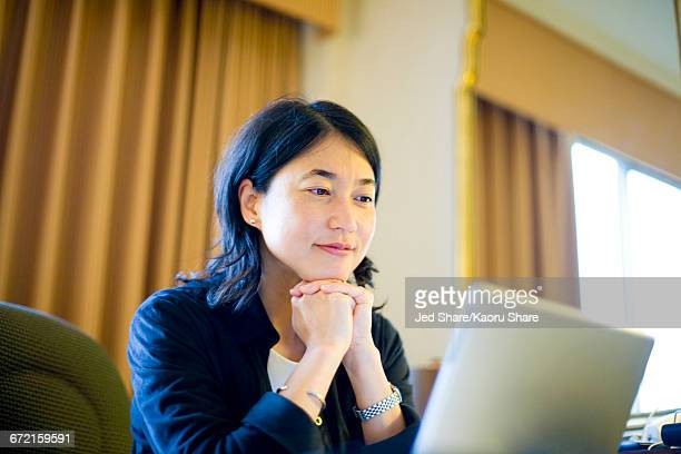 Smiling Japanese businesswoman reading laptop