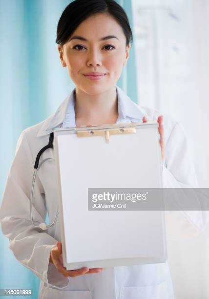 Smiling Japanese doctor holding medical record