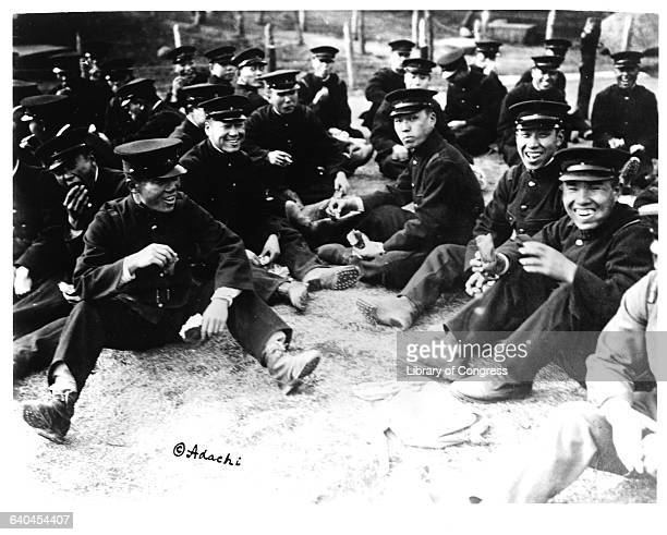 Smiling Japanese soldiers, prior to fighting in Siberia, sit on the ground and eat food.