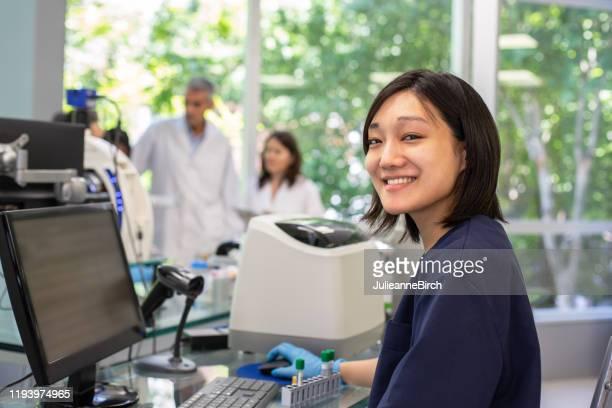 técnico japonés sonriente trabajando en laboratorio clínico - laboratorio clinico fotografías e imágenes de stock
