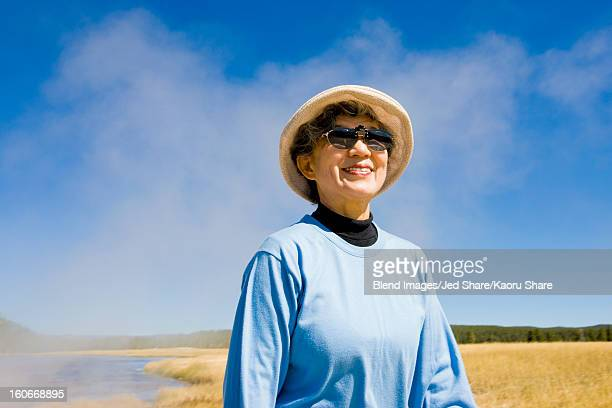smiling japanese woman standing near lake - blue hat stock pictures, royalty-free photos & images