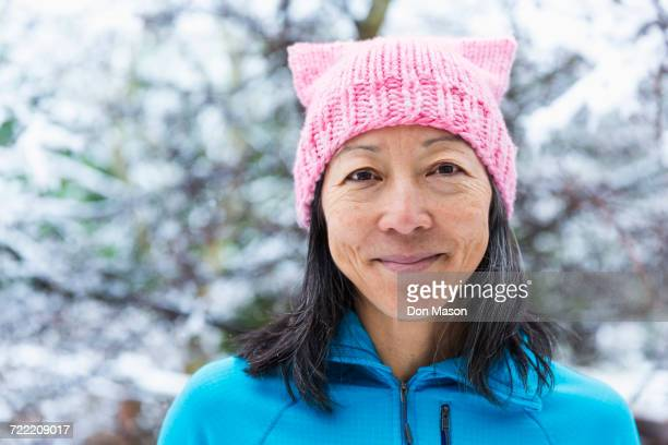 smiling japanese woman wearing pink hat with ears - asian 50 to 55 years old woman stock photos and pictures