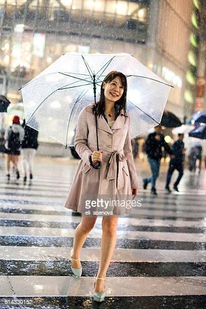 Smiling Japanese woman with umbrella crossing street in Shibuya, Tokyo