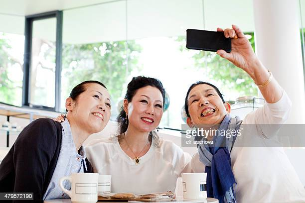 Smiling japanese women with smart phone taking selfie in cafe.
