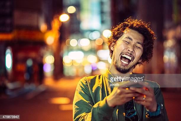 Smiling japanese young man with smart phone at night urban