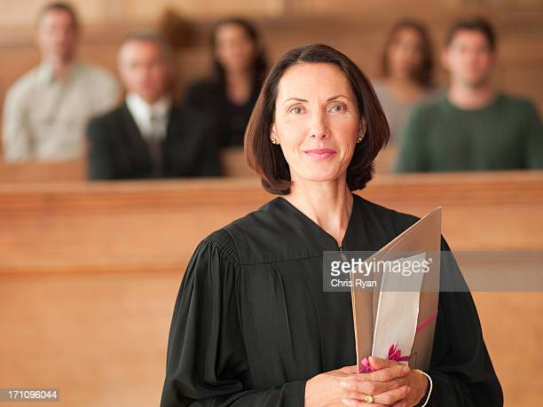 Smiling judge holding file in courtroom