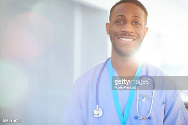 Smiling junior doctor in blue scrubs