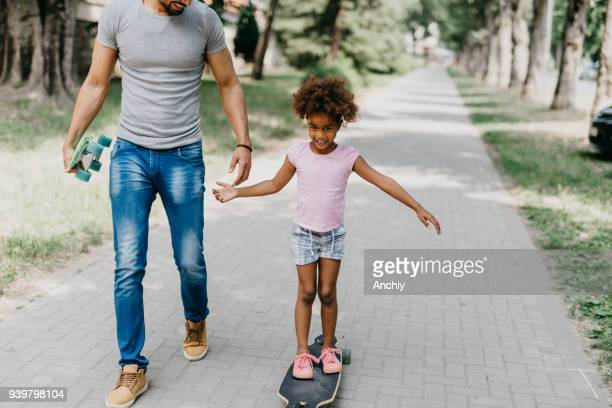 Smiling kid standing on longboard while holding her father's hand