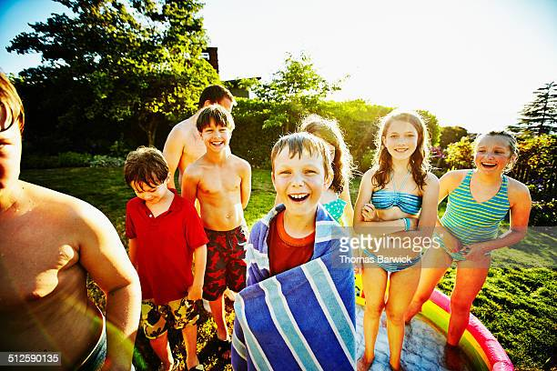 Smiling kids in swimsuits in backyard