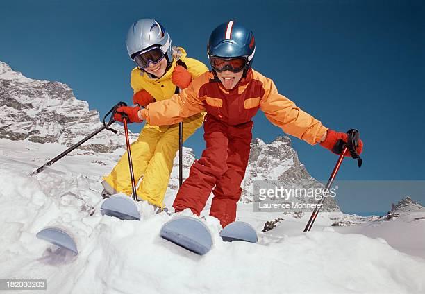 Smiling kids playing at ski in snow