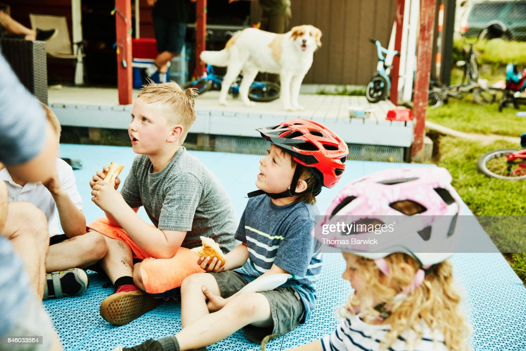 Smiling kids sitting on back porch of home eating hot dogs on summer evening : Stock Photo
