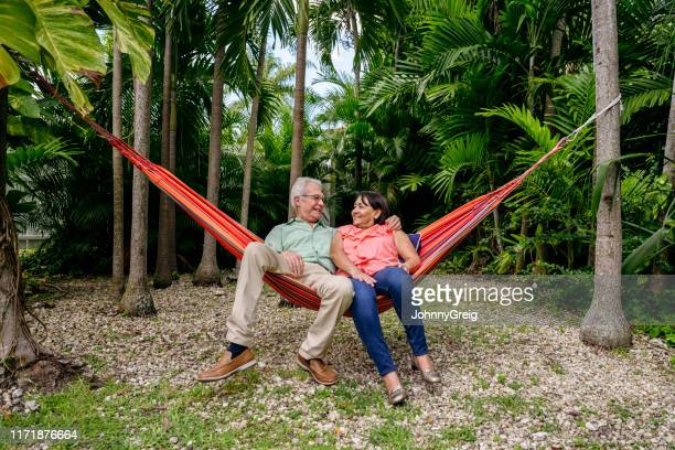 smiling latin american seniors reclining in backyard hammock - of miami photos stock pictures, royalty-free photos & images