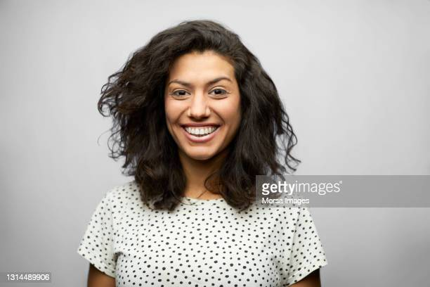 smiling latin american woman against gray background - latin american and hispanic ethnicity stock pictures, royalty-free photos & images