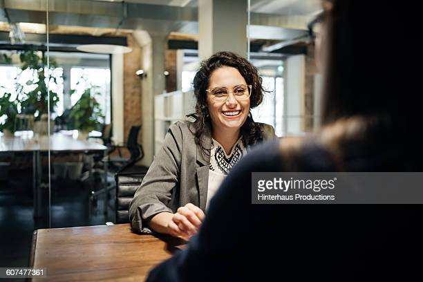 smiling latin businesswoman during a meeting - leanincollection stock pictures, royalty-free photos & images