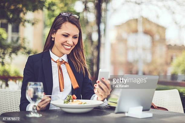Smiling Latin businesswoman text messaging