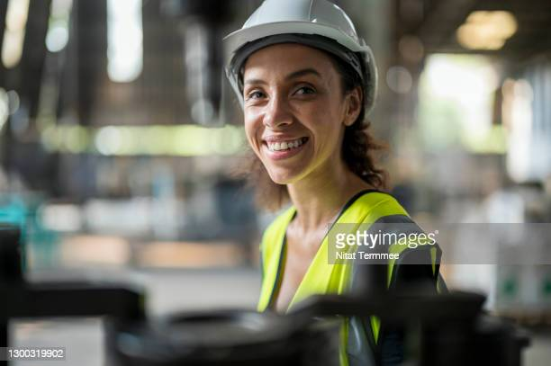 smiling latin women engineer in auto part factory. her is looking smart and confidence. - stem stock pictures, royalty-free photos & images