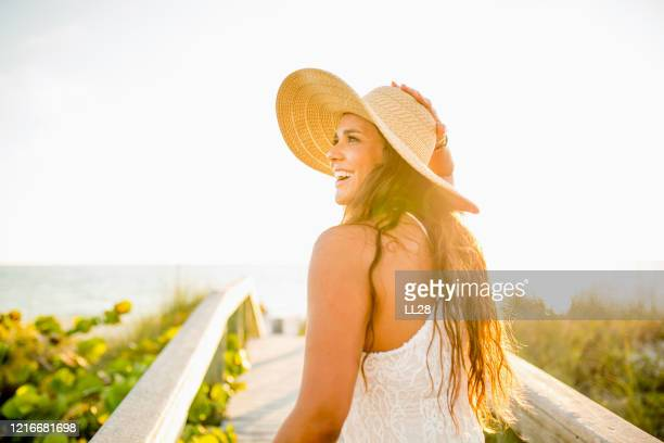 smiling latina walking towards the beach - gulf coast states stock pictures, royalty-free photos & images