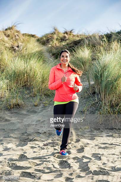 Smiling Latino Woman Running on Beach Trail