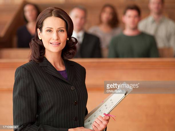 smiling lawyer holding file in courtroom - juror law stock pictures, royalty-free photos & images