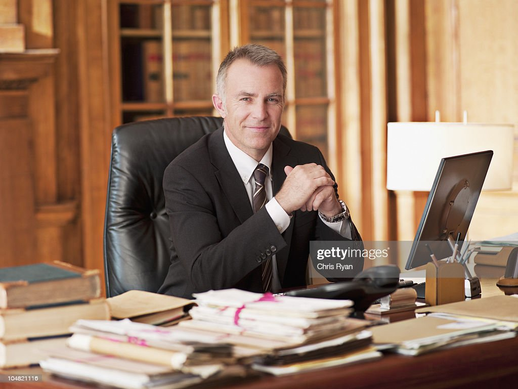 Smiling lawyer sitting at desk in office : Stock Photo