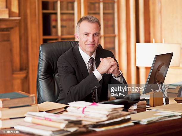smiling lawyer sitting at desk in office - law office stock photos and pictures