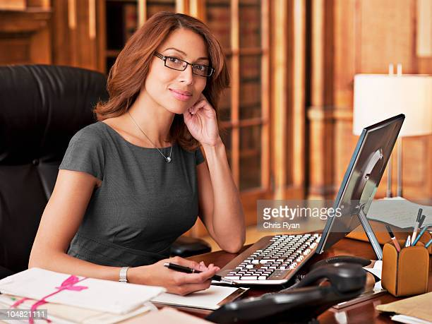 Smiling lawyer sitting at laptop in office