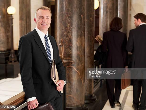 Smiling lawyer standing in corridor