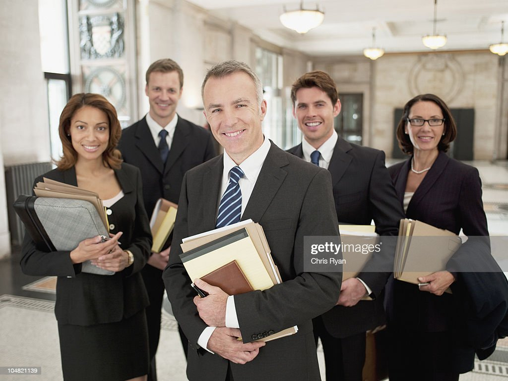 Smiling lawyers holding files in lobby : Stock Photo