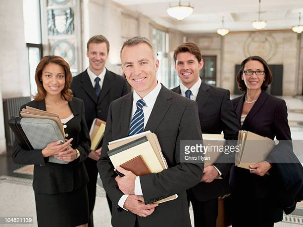 smiling lawyers holding files in lobby - legal system stock pictures, royalty-free photos & images