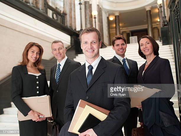 Smiling lawyers with files in lobby