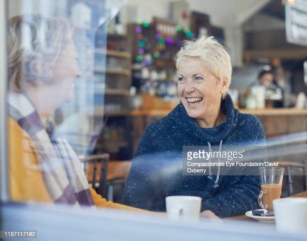 smiling lesbian couple drinking coffee and talking in cafe - candid stock pictures, royalty-free photos & images